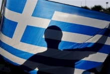 A nationalist holds a Greek flag during a protest against government plans to build the first official mosque in an Athens neighborhood